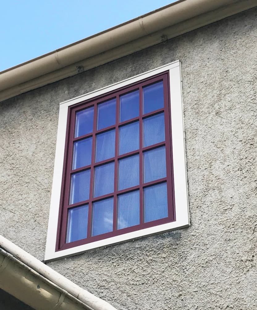 Exterior view of new wood window with red finish and traditional grille profile