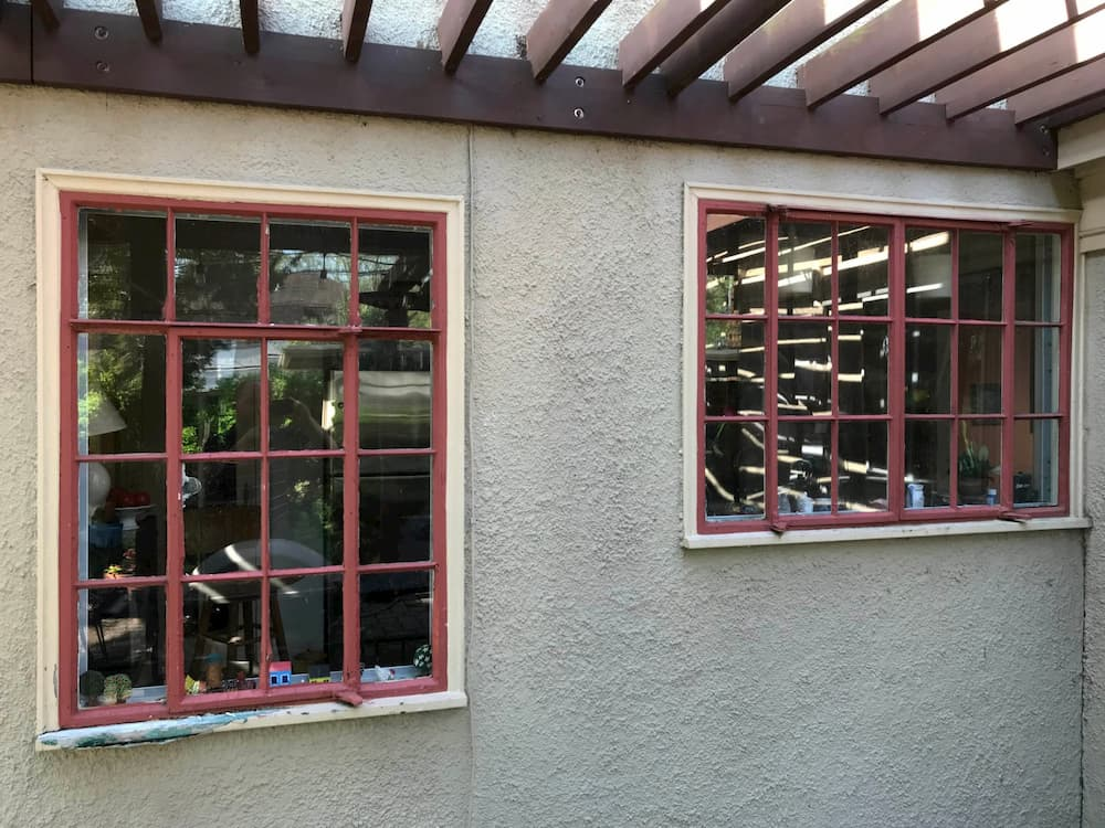 Exterior view of old peeling red windows
