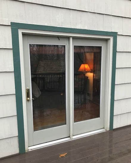 Exterior view of old hinged patio door on a home with white shingles.