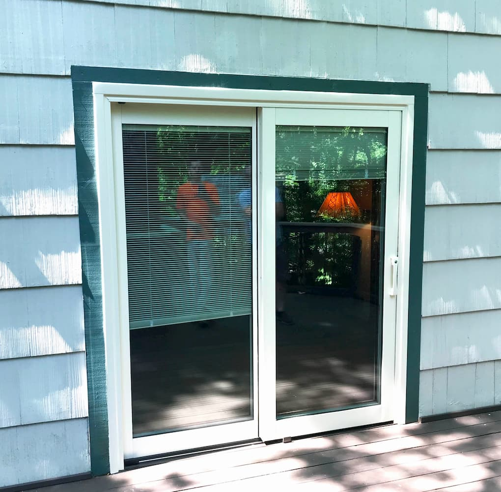 Exterior view of new white sliding patio door on a home with white shingles
