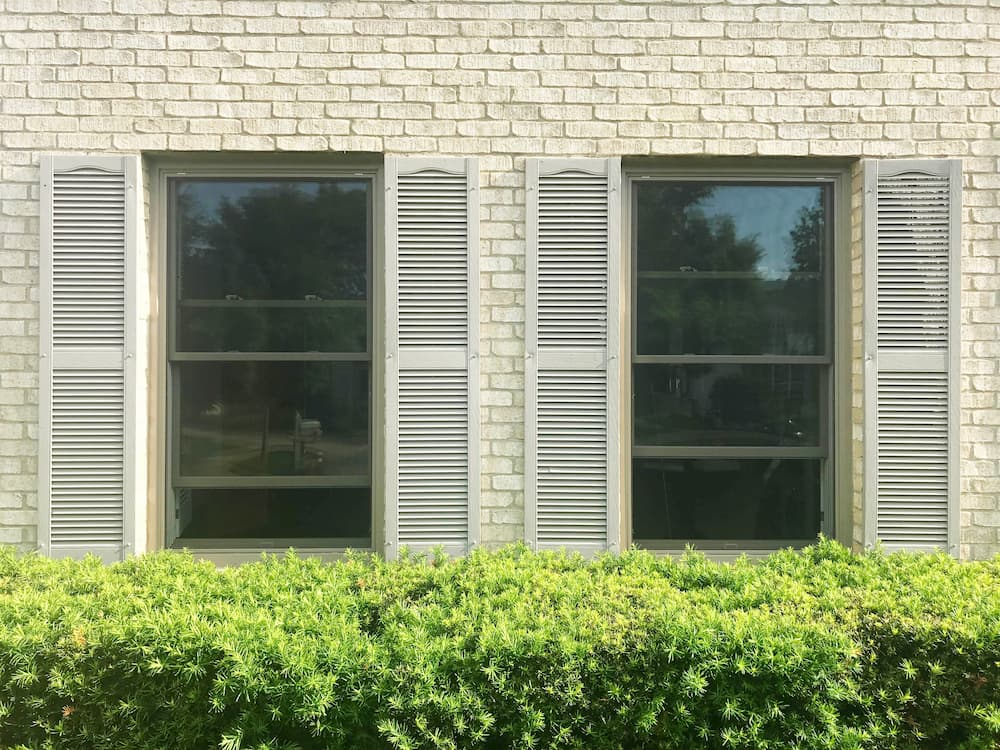 Two new wood double-hung windows with beige shutters on an ivory brick home