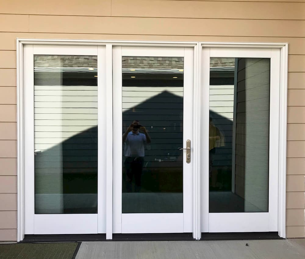 Exterior view of new wood hinged patio door on a home with tan siding