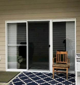 Exterior view of old sliding patio door on a home with tan siding