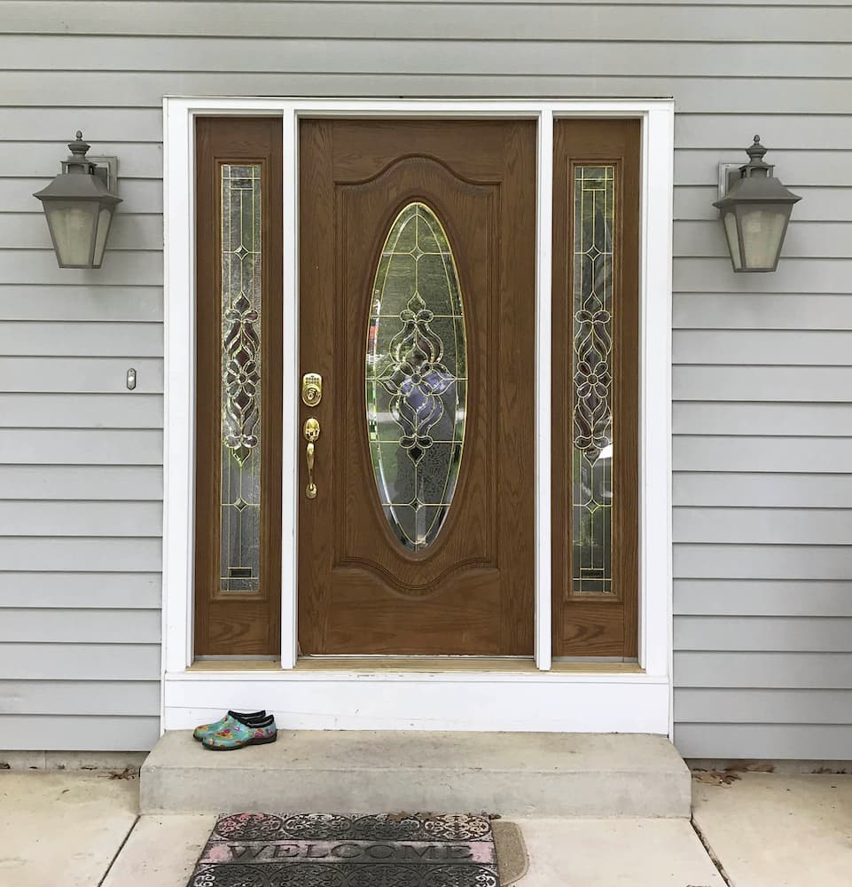 Old wood-look entry door with twin sidelights and decorative glass