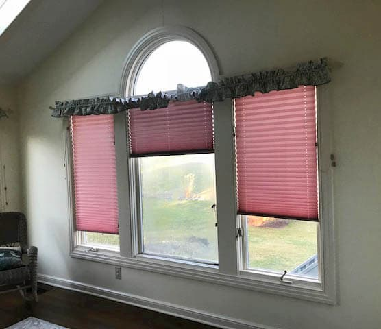Interior view old of three old casement windows with pink blinds