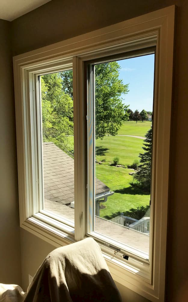 Interior photo of new wood side-by-side casement windows overlooking a golf course