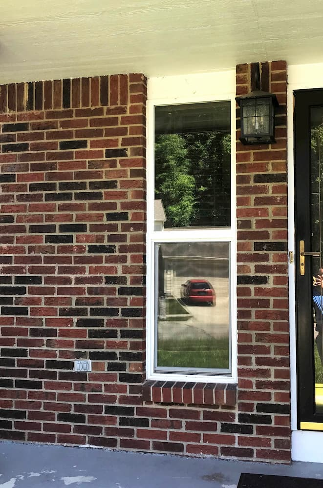 Narrow vinyl double-hung window on a red brick home