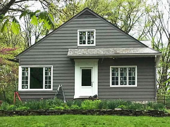 Exterior view of gray Cape Cod-style home with all-new wood casement windows