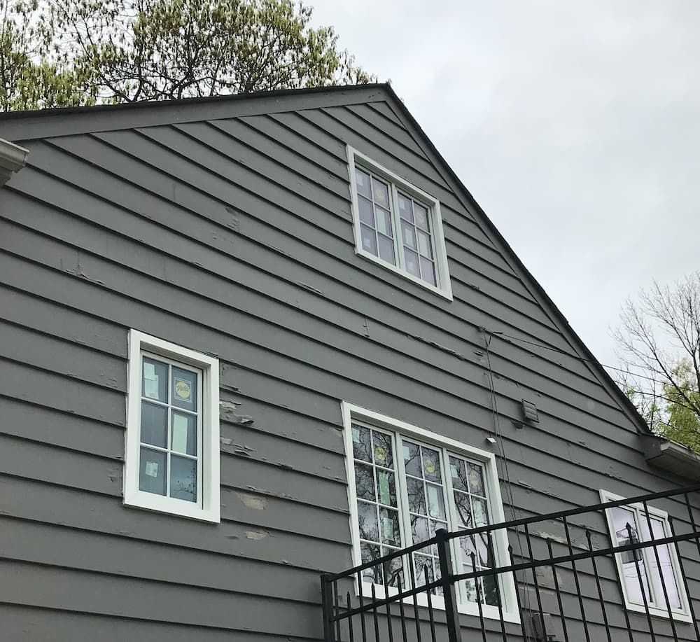 Exterior view of the side of a gray Cape Cod-style home with all-new wood casement windows