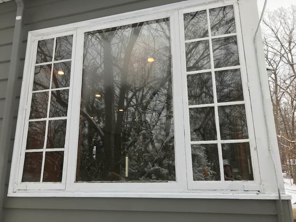 Exterior view of old wood casement and fixed windows on a gray home