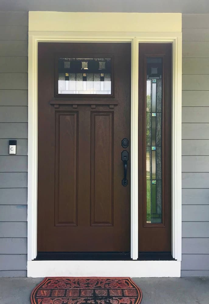 New Craftsman-style wood-look fiberglass entry door with decorative glass and sidelight