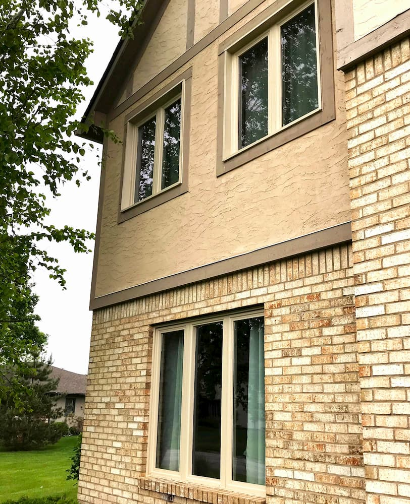 New vinyl casement windows in an almond exterior finish on the side of a Tudor-style home