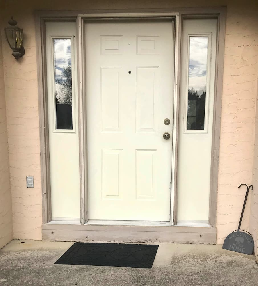 Old ivory entry door system on brick home