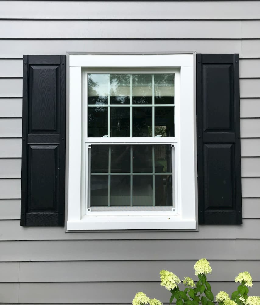 New white vinyl single-hung window with traditional grille pattern and black shutters on gray home