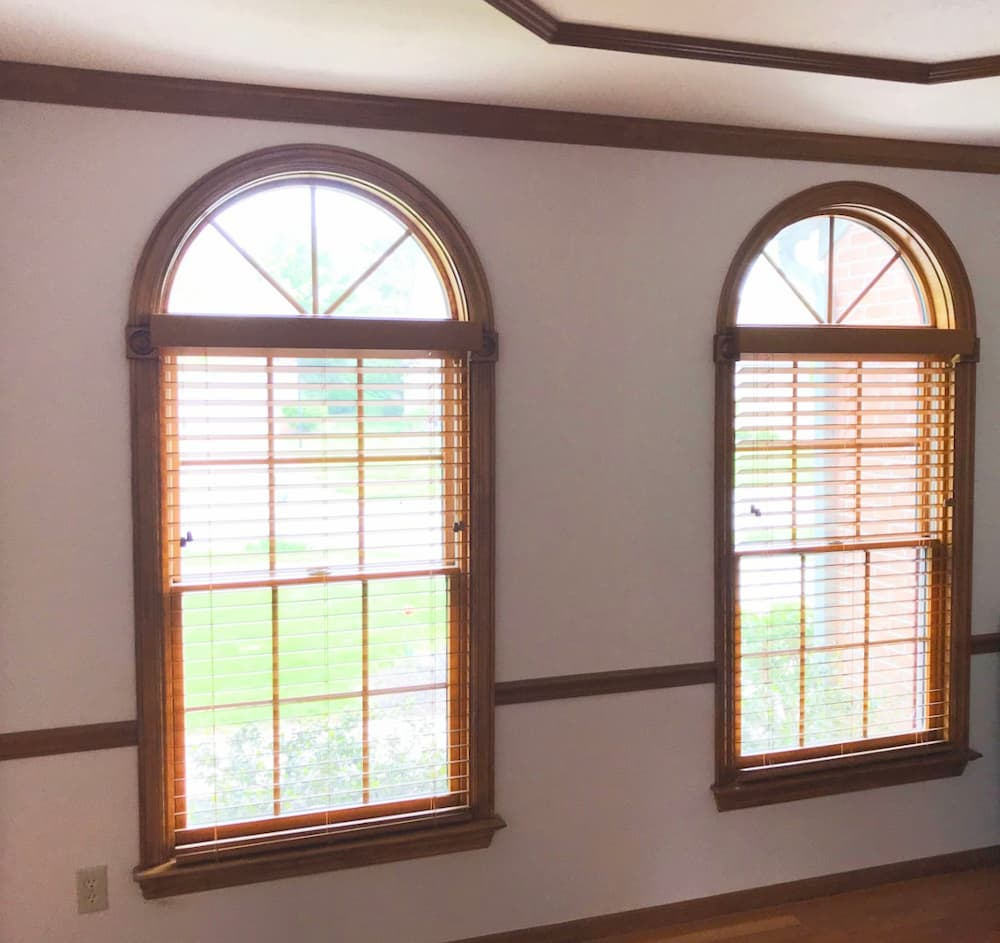 Two wood double-hung windows with half-circle transoms