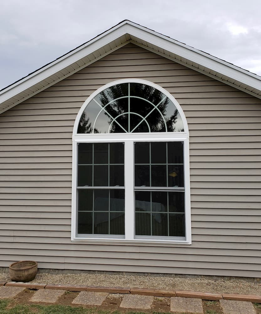 Exterior view of two new vinyl double-hung windows topped with a new arch window.