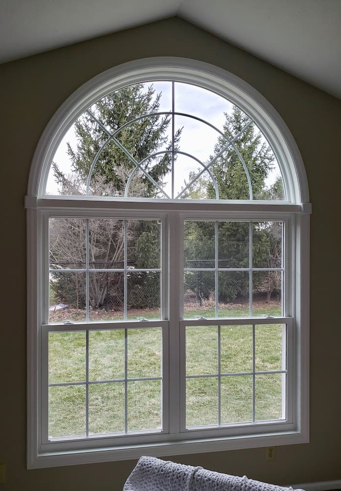 Interior view of two new vinyl double-hung windows topped with an arch window.