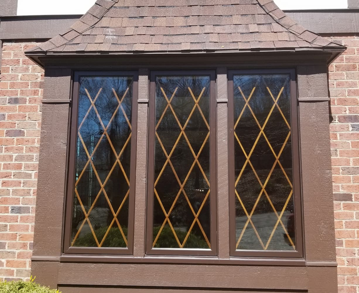 Exterior view of three new wood windows with diamond grille pattern