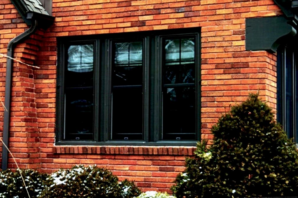 Exterior view of new wood double-hung windows against a red brick home.