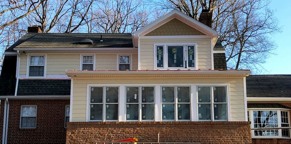 Exterior view of new addition with white wood double-hung windows