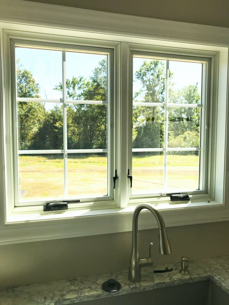 Interior view of two wood casement windows over a kitchen sink