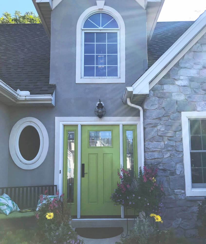 Front exterior view of gray home with new green fiberglass entry door with dual sidelights