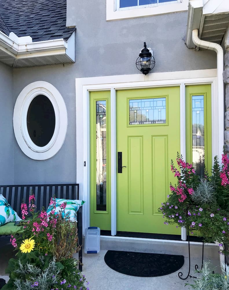 Exterior view of new green fiberglass entry door with decorative glass and dual sidelights