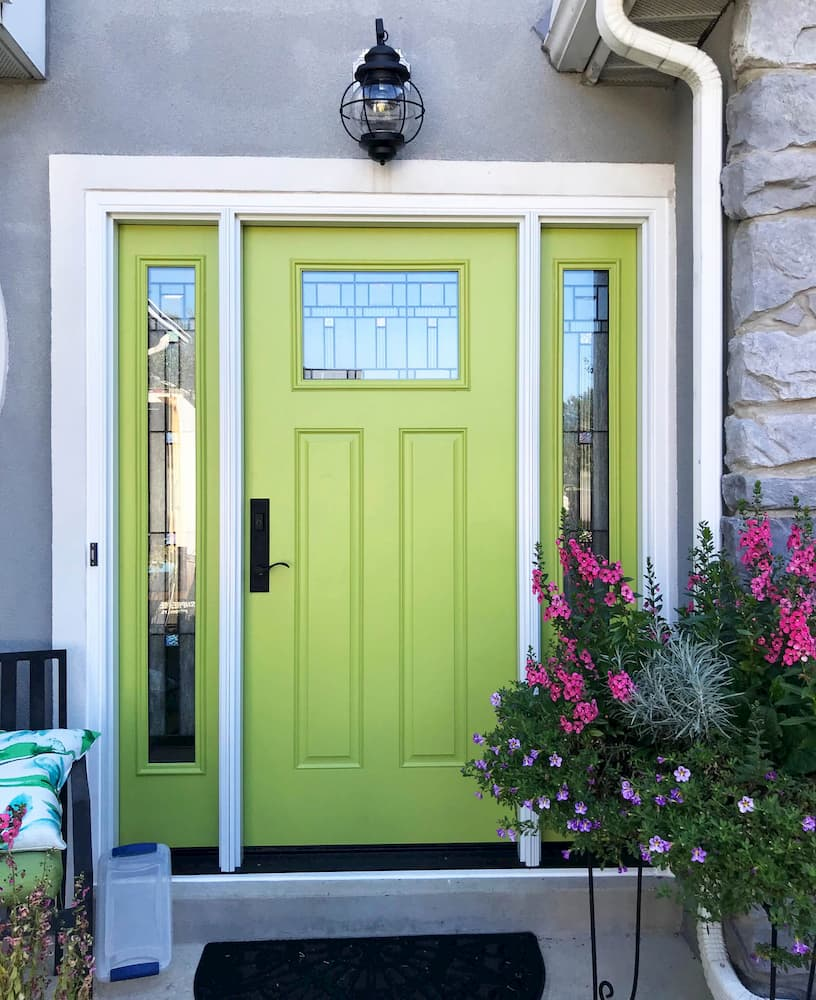 Exterior view of green fiberglass entry door with decorative glass and twin sidelights