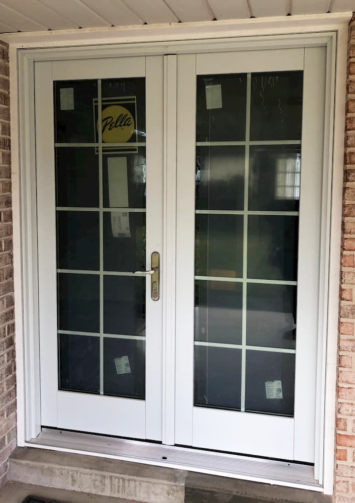 Exterior view white hinged French patio door with traditional grille pattern on brick home