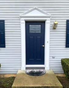 New blue fiberglass 2-panel 1/4 light entry door on home with white siding