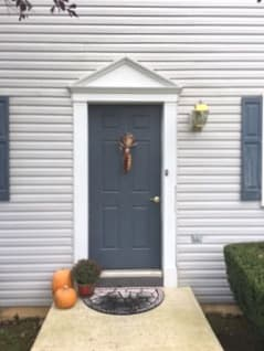 Old blue-gray 6-panel entry door on home with white siding