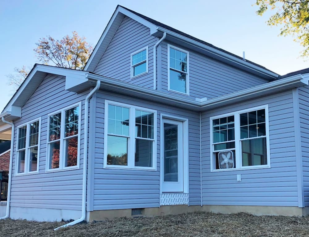 Exterior view of updated home with siding and white vinyl double-hung windows