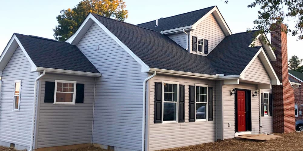 Exterior view of updated home with gray siding and white vinyl double-hung windows