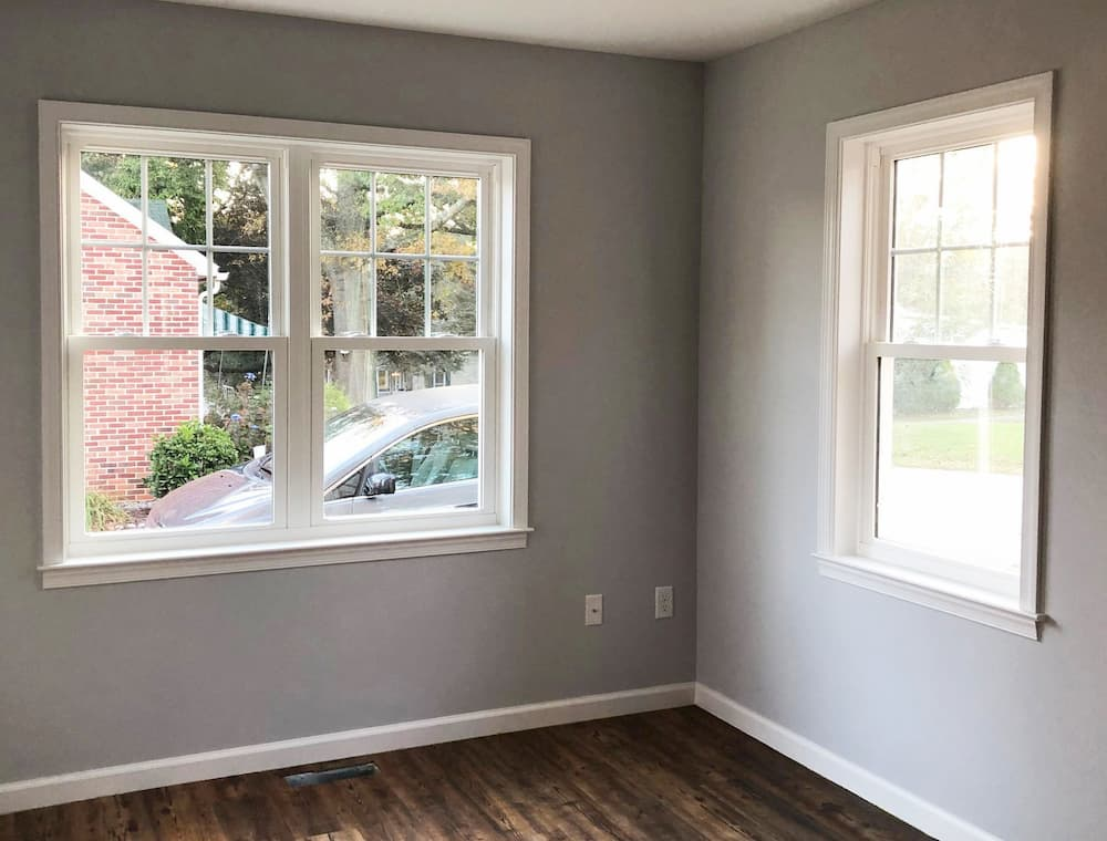 Interior view of a corner of a room with gray walls and new white vinyl double-hung windows