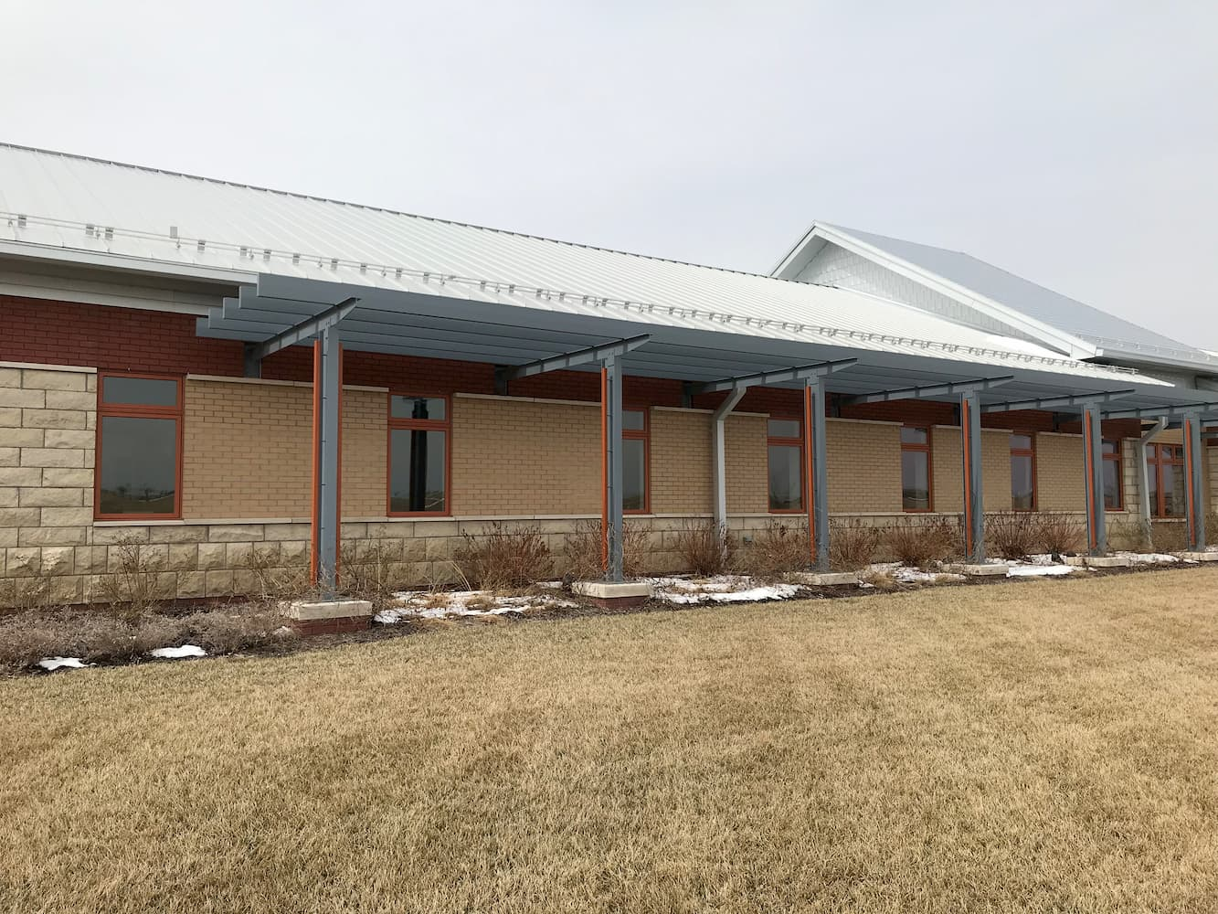 Long low commercial building on the prairie with fixed wood windows