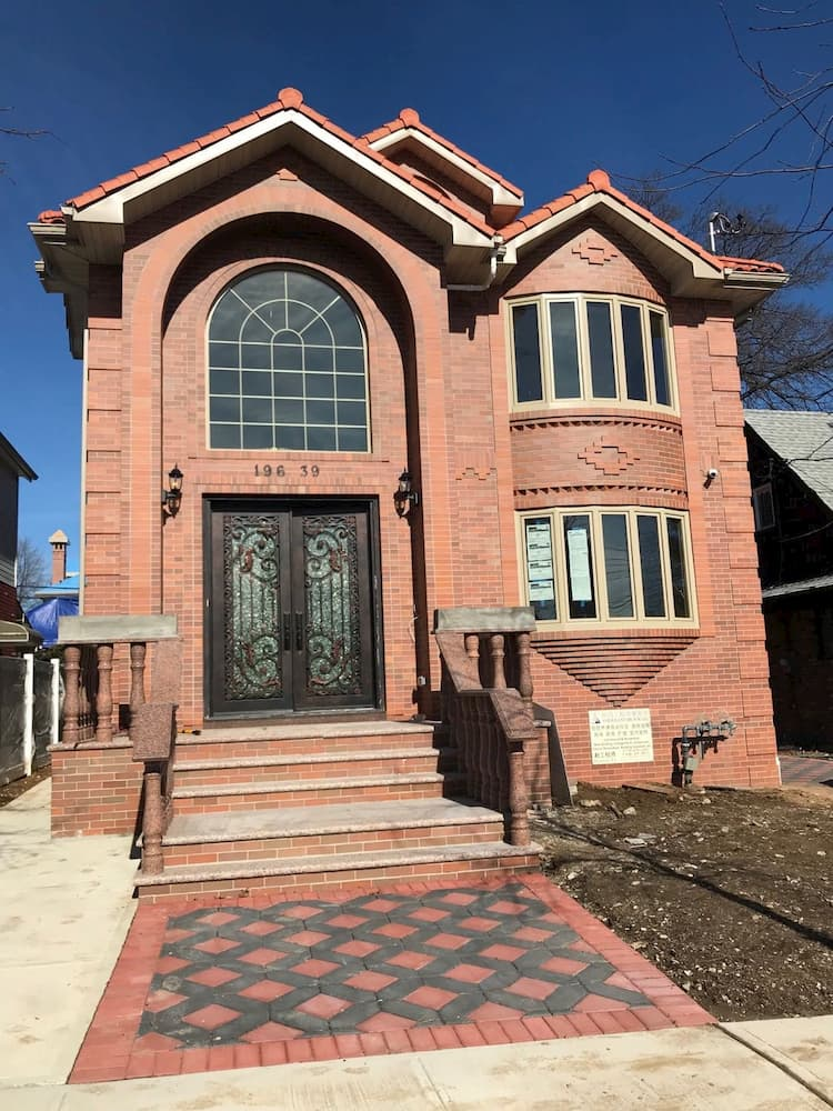 Red brick home with vinyl Palladian and bow windows.