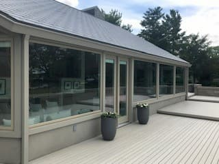 Exterior view of deck and large fixed wood windows with aluminum cladding