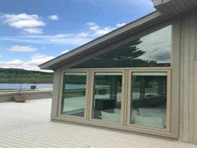 Exterior view of deck with lifestyle series fixed wood windows with a view of a lake