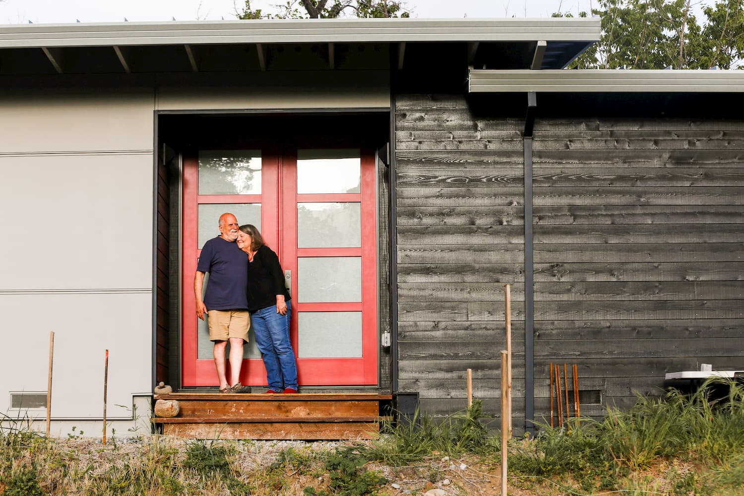 Couple standing in front of contemporary red double entry doors