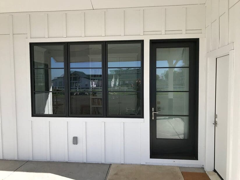 New fiberglass entry door and wood casement windows with contemporary grilles and black finish