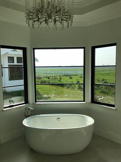 Bathroom with wood casement and fixed windows with contemporary grille pattern and black finish