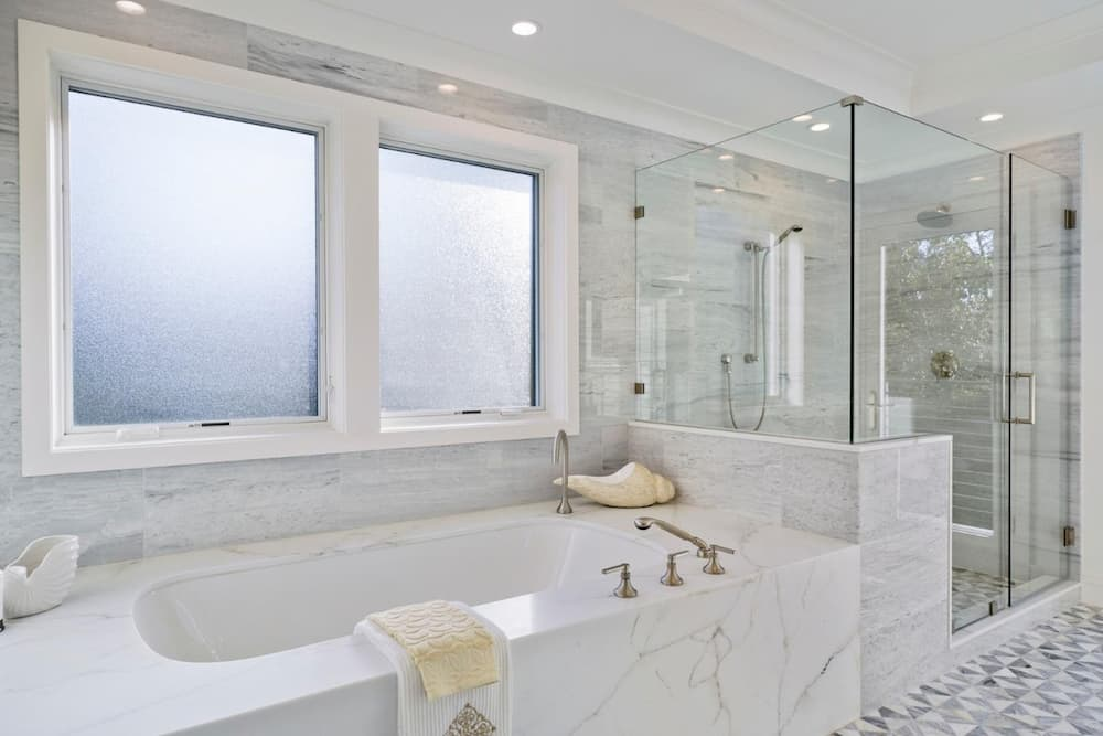 Two wood casement windows with frosted glass above a bathtub in a bathroom