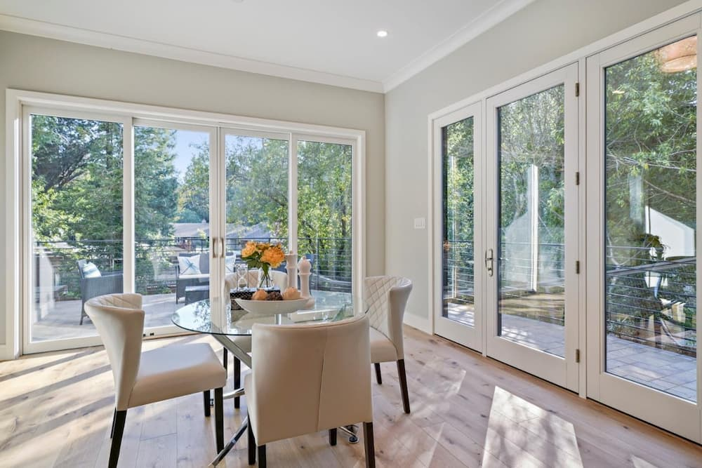 Breakfast room with wood sliding glass patio doors and a hinged patio door with fixed glass panels