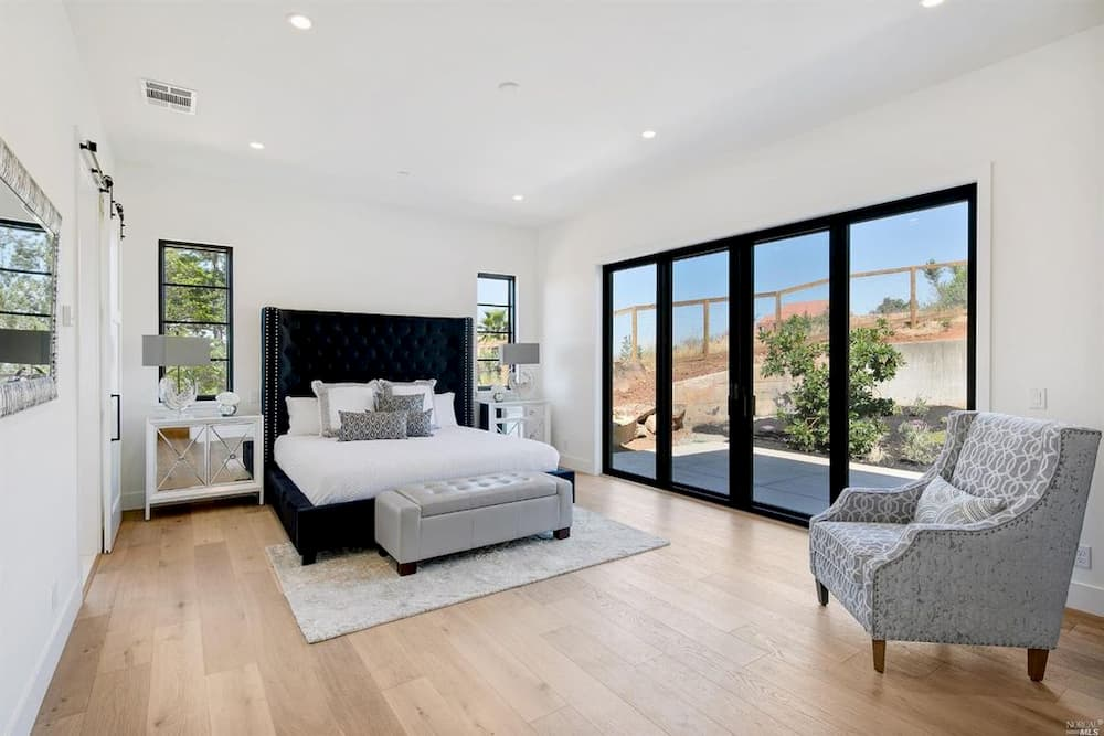 Bedroom with contemporary wood sliding patio doors in a black finish