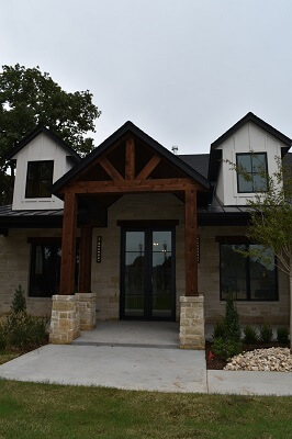 front door of new construction edmond ok home with wood casemen windows