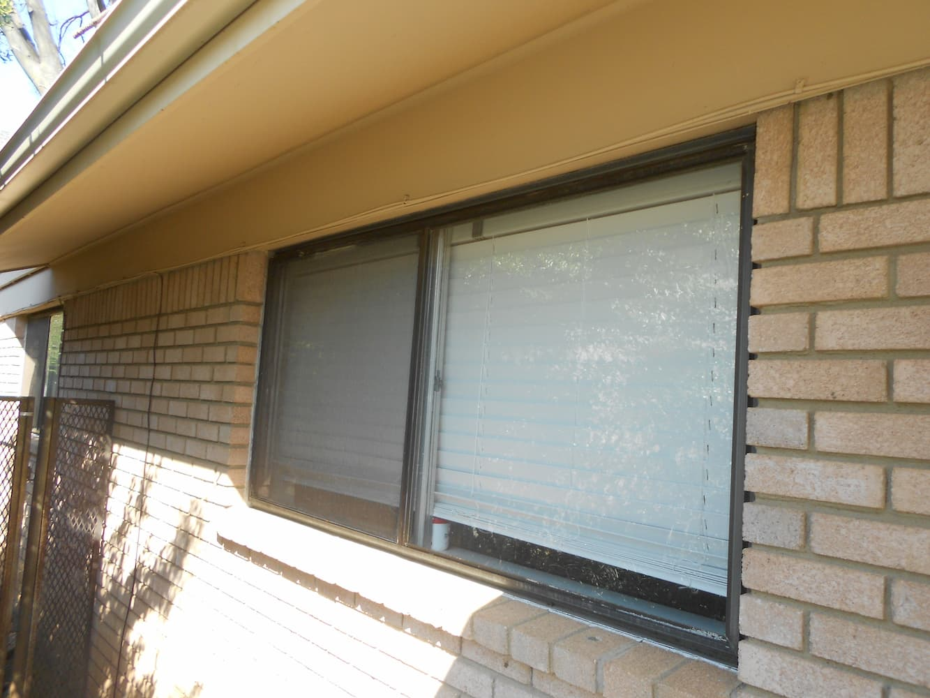 Exterior view of small casement windows with blinds