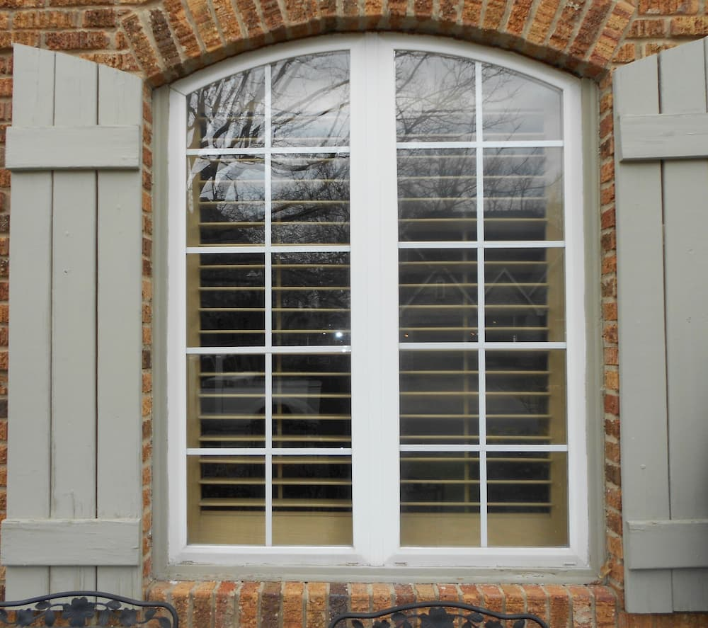 Special shape window with traditional grille pattern and gray shutters