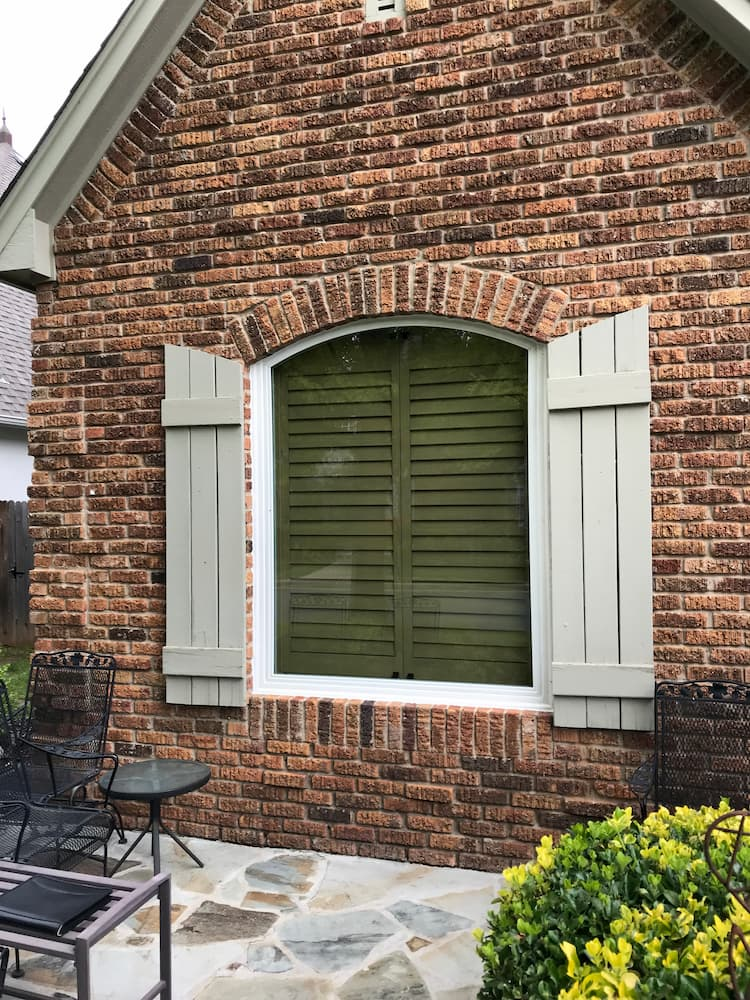 Exterior view of new special shape fiberglass picture window framed by gray shutters