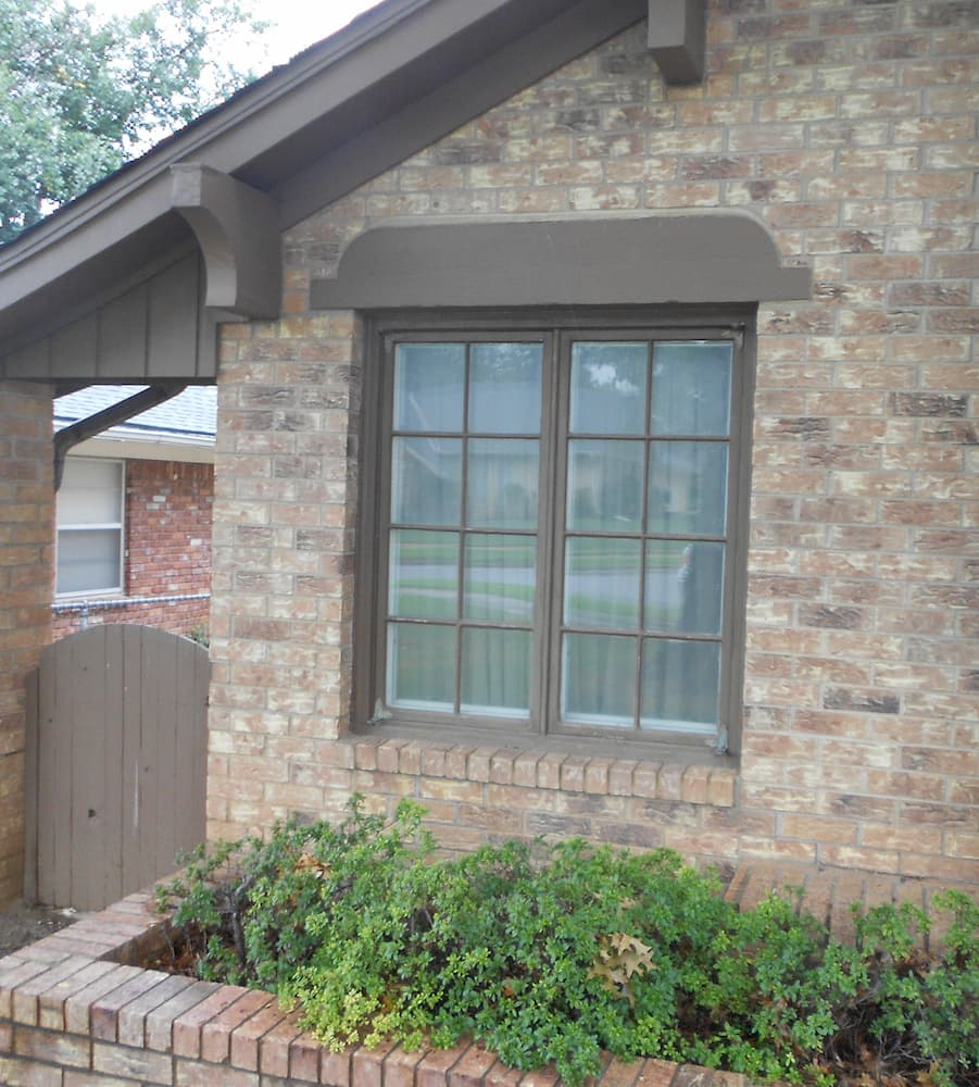 Two old wood casement windows painted brown on a brick home