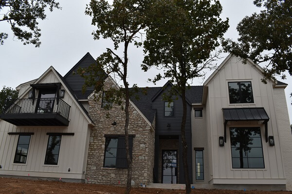 back view of edmond ok new construction home with wood casement windows